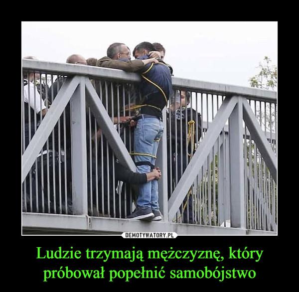 Ludzie trzymają mężczyznę, którypróbował popełnić samobójstwo –